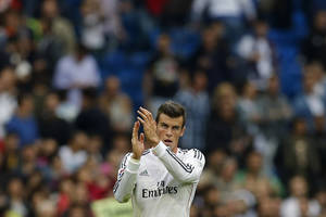 Photo - Real Madrid's Gareth Bale from Great Britain, claps,  during a Spanish La Liga soccer match against Malaga at the Santiago Bernabeu stadium in Madrid, Spain, Saturday, Oct. 19, 2013. (AP Photo/Andres Kudacki)