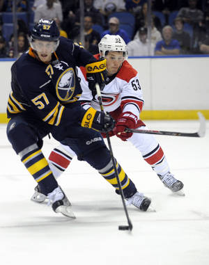 Photo - Buffalo Sabres defenseman Tyler Myers (57) steals the puck from Carolina Hurricanes center Jeff Skinner (53) during the second period of an NHL hockey preseason game in Buffalo, N.Y., Thursday, Sept. 19, 2013. (AP Photo/Gary Wiepert)