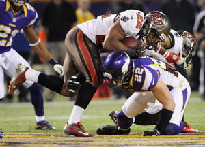 Photo -   Tampa Bay Buccaneers running back Doug Martin, left, runs over Minnesota Vikings free safety Harrison Smith during the second half of an NFL football game Thursday, Oct. 25, 2012, in Minneapolis. (AP Photo/Jim Mone)