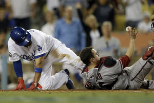 Photo -   Arizona Diamondbacks catcher Miguel Montero, right, shows the umpire the ball after forcing Los Angeles Dodgers' Shane Victorino out at the plate during eighth inning of a baseball in Los Angeles, Saturday, Sept. 1, 2012. (AP Photo/Chris Carlson)