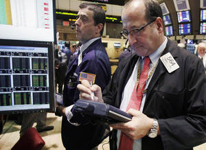 Photo -   In this Tuesday, Oct. 9, 2012 photo, traders Stephen Guilfoyle, left, and Edward Landi work on the floor of the New York Stock Exchange. Stock futures are mixed Wednesday, Oct. 10, 2012, a day after the U.S. earning season kicked off. (AP Photo/Richard Drew)