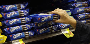 Photo - FILE - In this Feb. 9, 2011 file photo, a shopper selects Oreo cookies at a Ralphs Fresh Fare supermarket in Los Angeles. Mondelez International Inc. reports quarterly financial results after the market closes on Wednesday, Feb. 12, 2014. (AP Photo/File)