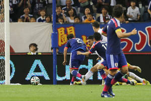 Photo - Japan's Atsuto Uchida (2) scores a goal against Cyprus during a friendly soccer match in Saitama, north of Tokyo, Tuesday, May 27, 2014. Japan will play against Ivory Coast, Greece and Colombia in Group C of the World Cup 2014 in Brazil. (AP Photo/Shuji Kajiyama)