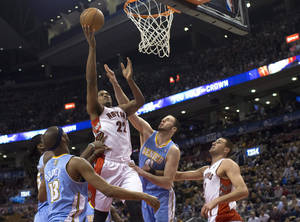 photo - Toronto Raptors' Rudy Gay (22) scores on Denver Nuggets' Corey Brewer, left, and Kosta Koufos as Raptors' Jonas Valanciunas watches during the first half of an NBA basketball game in Toronto on Tuesday, Feb. 12, 2013. (AP Photo/The Canadian Press, Chris Young)