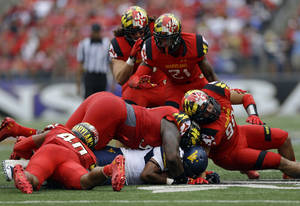 Photo - West Virginia running back Charles Sims, bottom, is tackled by a pack of Maryland defenders in the first half of an NCAA college football game in Baltimore, Saturday, Sept. 21, 2013. (AP Photo/Patrick Semansky)