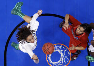 Photo - Baylor's Brittney Griner (42) and Louisville forward Monique Reid (33) reach for a rebound in the first half of a regional semifinal in the women's NCAA college basketball tournament in Oklahoma City, Sunday, March 31, 2013. Louisville won 82-81. (AP Photo/Sue Ogrocki)