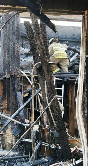 Photo - An Oklahoma City fireman climbs through the damage at Cash Express, 3630 N Western. The loan company caught fire early Thursday. Photo by Paul B. Southerland, The Oklahoman ORG XMIT: KOD <strong>PAUL B. SOUTHERLAND - PAUL B. SOUTHERLAND</strong>