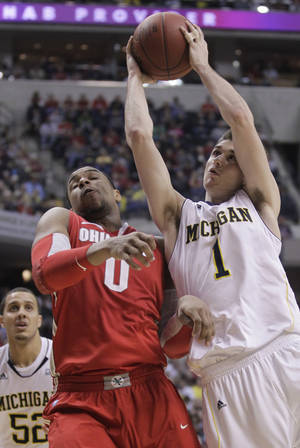 Photo -   Michigan guard Stu Douglass (1) takes a shot against Ohio State forward Jared Sullinger (0) in the first half of an NCAA college basketball game in the semifinals of the Big Ten Conference tournament in Indianapolis, Saturday, March 10, 2012. At left is Michigan forward Jordan Morgan. (AP Photo/Michael Conroy)