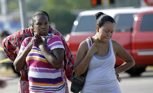 Photo - Parents,  Eunice Pacheco, right, and LaKesia Brent, left, wait for news about their children outside Spring High School Wednesday, Sept. 4, 2013, in Spring, Texas.  A 16-year-old boy has been airlifted from the school in suburban Houston with stab wounds suffered in an altercation at the campus. The Harris County Sheriff's Office says it responded about 7 a.m. Wednesday to Spring High School to a report of a stabbing. Spring is about 20 miles north of Houston.  (AP Photo/David J. Phillip)