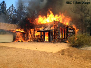 Photo - In this still frame from video provided by KNSD-TV, a home is fully involved in flames as crews scrambled to corral a wildfire that burned two homes near the San Diego County mountain town of Julian in Southern California Thursday, July 3, 2014. The blaze erupted around 10:30 a.m. and prompted the mandatory evacuation of 200 homes. Firefighters attacked the 150-acre blaze in the air and on the ground. The fire destroyed two homes and an outbuilding and was 15 percent contained at nightfall, state fire Capt. Kendal Bortisser said. (AP Photo/KNSD-TV)