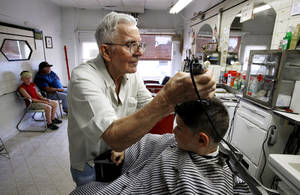 photo - John Adkins gives a haircut to Colby Wyatt, 8, in his barbershop Tuesday in Maysville. Adkins cut hair for  Colby's grandfather, Paul Arnold, when Arnold was 3 years old. Arnold is seated left with another grandson, Kaedon Wyatt, 10. Photo by Steve Sisney, The Oklahoman