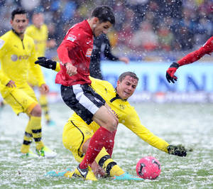 Photo -   Freiburg's Mensur Mujdza, left, and Dortmund's Mario Goetze challenge for the ball during the German Bundesliga soccer match between SC Freiburg and Borussia Dortmund in Freiburg, southern Germany, Saturday Oct. 27, 2012. (AP Photo/dapd/ Michael Kienzler)