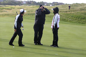 "Photo -   A rules official holds onto his hat as he talks to unidentified golfers about the suspension of play during day two of the Women's British Open at the Royal Liverpool Golf Course, in Hoylake, England, Friday Sept. 14, 2012. Play was suspended after about an hour of play because of strong winds that disrupted the second round so badly that organizers declared early scores ""null and void."" With winds gusting to 60 mph, all the players struggled and American Cristie Kerr had her ball blown off the 12th tee three times. (AP Photo / Peter Byrne, PA) UNITED KINGDOM OUT - NO SALES - NO ARCHIVES"