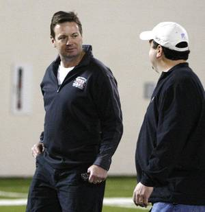 Photo - Oklahoma head coach Bob Stoops, left, talks with Paul Guenther, left, of the Cincinnati Bengals at Oklahoma's Pro Day footbal workout in Norman, Okla., Tuesday, March 8, 2011. (AP Photo/Sue Ogrocki) <strong>Sue Ogrocki</strong>