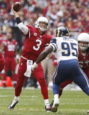 Photo - Arizona Cardinals quarterback Carson Palmer (3) throws under pressure from St. Louis Rams defensive end William Hayes (95) during the first half of an NFL football game, Sunday, Dec. 8, 2013, in Glendale, Ariz. (AP Photo/Ross D. Franklin)