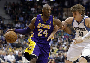 Photo - Los Angeles Lakers' Kobe Bryant, left, drives past Minnesota Timberwolves' Andrei Kirilenko of Russia in the second half of an NBA basketball game Wednesday, March 27, 2013 in Minneapolis. Bryant led the Lakers with 31 points in their 120-117 win. (AP Photo/Jim Mone)