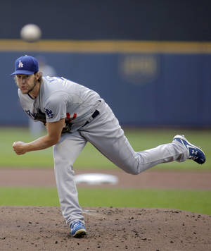 Photo - Los Angeles Dodgers pitcher Clayton Kershaw delivers to the Milwaukee Brewers during the first inning of a baseball game Sunday, Aug. 10, 2014, in Milwaukee. (AP Photo/Darren Hauck)