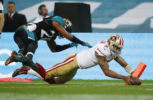 Photo - San Francisco 49ers quarterback Colin Kaepernick (7) scores a 12-yard touchdown while being pursued by Jacksonville Jaguars free safety Josh Evans (26) during the NFL football game at Wembley Stadium, London, Sunday, Oct. 27, 2013.  (AP Photo/Matt Dunham)
