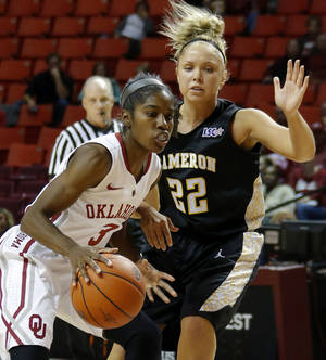 Photo - Oklahoma's Aaryn Ellenberg goes around Cameron's Jade Herl during an NCAA women's college exhibition basketball game between the University of Oklahoma and Cameron University at Lloyd Noble Center in Norman, Okla., on Saturday, Nov. 2, 2013. Photo by Bryan Terry, The Oklahoman
