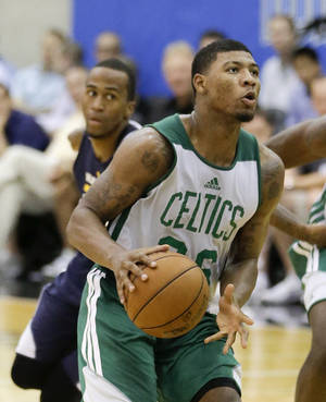 Photo - Boston Celtics'  Marcus Smart, right,  looks to shoot as he gets past Indiana Pacers' Dee Bost, left, during an NBA summer league basketball game in Orlando, Fla., Monday, July 7, 2014. (AP Photo/John Raoux)