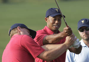Photo - United States team player Tiger Woods, right, helps team player Steve Stricker with his swing before a team photo for the Presidents Cup golf tournament at Muirfield Village Golf Club Wednesday, Oct. 2, 2013, in Dublin, Ohio. (AP Photo/Jay LaPrete)