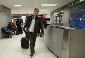 Photo - Jordan Houlton, of Toronto, walks through Kennedy International Airport en route to a connecting flight to Mexico after the Delta flight from Toronto he was on skidded off the runway into a snow bank,  Sunday, Jan. 5, 2014, in New York.  Houton said he slept through the incident. (AP Photo/Kathy Willens)