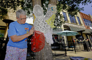 Photo - Paula Nightengale stitches together doilies around a tree for the Yarnover Enid community art event on Friday.  Photo by Chris Landsberger, The Oklahoman <strong>CHRIS LANDSBERGER - CHRIS LANDSBERGER</strong>