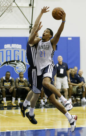 Photo - Oklahoma City Thunder's Andre Roberson (21) drives in for a shot as Indiana Pacers' Jake Odum tries to defend during an NBA summer league basketball game in Orlando, Fla., Wednesday, July 9, 2014. (AP Photo/John Raoux)