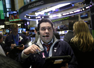 """Photo - A trader works on the floor at the New York Stock Exchange in New York, Wednesday, Jan. 2, 2013. The """"fiscal cliff"""" compromise, for all its chaos and controversy, was enough to send the stock market shooting higher Wednesday, the first trading day of the new year. (AP Photo/Seth Wenig)"""