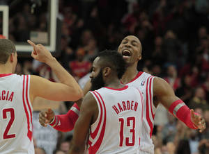 Photo - Houston Rockets center Dwight Howard, right, celebrates with teammates James Harden (13) and Francisco Garcia, left, after scoring to defeat the Washington Wizards 113-112 at the end of an NBA basketball game in Houston, Wednesday, Feb. 12, 2014. (AP Photo/Richard Carson)