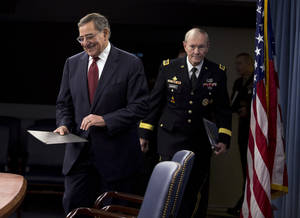 Photo - Defense Secretary Leon Panetta, followed by Joint Chiefs Chairman Gen. Martin Dempsey, arrive for their news conference at the Pentagon, Thursday, Jan. 10, 2013. Panetta said he is asking his department to begin taking steps to freeze civilian hiring, delay some contract awards and curtail some maintenance to prepare for drastic budget cuts if Congress can't reach an agreement on a final spending plan.  (AP Photo/ Evan Vucci)
