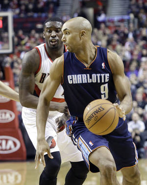 Photo - Charlotte Bobcats guard Gerald Henderson, right, drives past Portland Trails Blazers guard Wesley Matthews during the first half of an NBA basketball game in Portland, Ore., Thursday, Jan. 2, 2014. (AP Photo/Don Ryan)