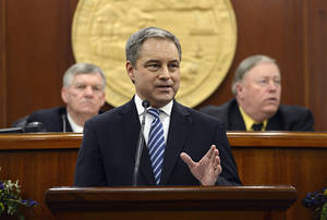Photo - Alaska's Republican Gov. Sean Parnell, center, leads a round of applause for U.S. service members in front of the Alaska State Legislature during his annual State of the State address in Juneau, Alaska Wednesday, Jan. 16, 2013. Also pictured at left, Senate President Charlie Huggins, R- Wasilla, and House Speaker Mike Chenault, R- Nikiski. (AP Photo/Chris Miller)codes