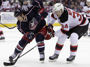Photo - Columbus Blue Jackets' Cam Atkinson, left, carries the puck across the blue line as New Jersey Devils' Jon Merrill defends during the second period of an NHL hockey game Tuesday, Dec. 10, 2013, in Columbus, Ohio. (AP Photo/Jay LaPrete)