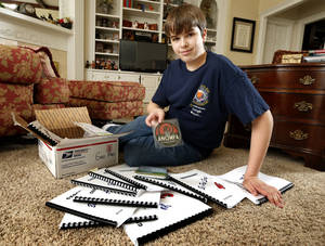 Photo - Matthew Armor shows some of the geography material he studied before traveling to Washington for the National Geographic Bee. PHOTO BY STEVE SISNEY, THE OKLAHOMAN <strong>STEVE SISNEY</strong>