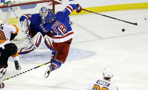 photo - New York Rangers' Marc Staal (18) reacts after being hit by a puck during the third period of an NHL hockey game against the Philadelphia Flyers on Tuesday, March 5, 2013, in New York. Rangers goalie Henrik Lundqvist, of Sweden, watches. The Rangers won the game 4-2. (AP Photo/Frank Franklin II)