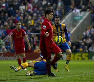 photo - Liverpool's Luis Suarez, centre, appears to handle the ball as he scores against Mansfield Town during their English FA Cup 3rd round soccer match at Field Mill Stadium, Mansfield, England, Sunday, Jan. 6, 2013. (AP Photo/Jon Super)