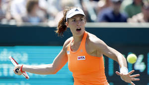 Photo - Andrea Petkovic, of Germany, returns to Eugenie Bouchard, of Canada, during the Family Circle Cup tennis tournament in Charleston, S.C., Saturday, April 5, 2014. Petkovic won 1-6, 6-3, 7-5. (AP Photo/Mic Smith)
