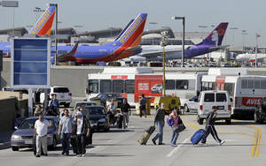 Photo - Passengers walk with their luggage leaving the Los Angeles International Airport on Friday Nov. 1, 2013. A suspected gunman was in custody Friday following a shooting at Los Angeles airport that left multiple people wounded and disrupted flights nationwide. (AP Photo/Reed Saxon)