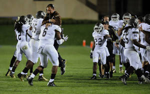 Photo - Western Michigan's head coach P.J. Fleck  leaps on the back of Roosevelt Donaldson (6) during the first quarter of an NCAA college football game against Northwestern in Evanston, Ill., Saturday, Sept. 14, 2013. (AP Photo/Matt Marton)
