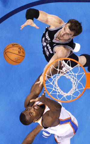 Photo - San Antonio Spurs center Tiago Splitter (22) and Oklahoma City Thunder forward Serge Ibaka reach for a rebound in the second quarter of Game 4 of the Western Conference finals NBA basketball playoff series in Oklahoma City, Tuesday, May 27, 2014. (AP Photo/Sue Ogrocki)