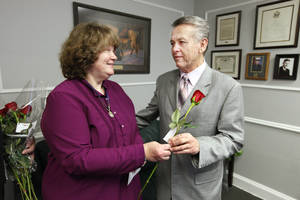 Photo - State Sen. Bill Brown, R-Broken Arrow, accepts a rose from Brenda Moyse, of Broken Arrow, in his office during the 2013 Rose Day sanctity of life activities at the state Capitol.  <strong>PAUL B. SOUTHERLAND - PAUL B. SOUTHERLAND</strong>