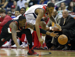 Photo - Portland Trail Blazers guard Wesley Matthews (2) and Washington Wizards forward Trevor Ariza (1) go for the loose ball in the first half of an NBA basketball game, Monday, Feb. 3, 2014, in Washington. (AP Photo/Alex Brandon)