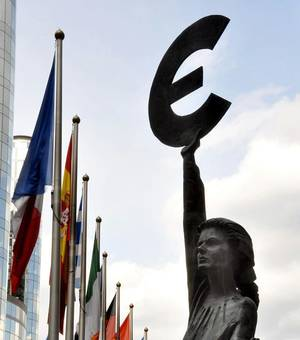 Photo - This statue, just outside the European Parliament in Brussels, holds the symbol of the euro — Europe's common currency. Photo by Cameron Hewitt