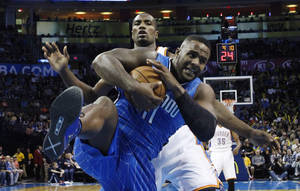 Photo - Orlando Magic forward Glen Davis (11) grabs a rebound in front of Oklahoma City Thunder forward Serge Ibaka (9) in the first quarter of an NBA basketball game in Oklahoma City, Sunday, Dec. 15, 2013. (AP Photo/Sue Ogrocki)