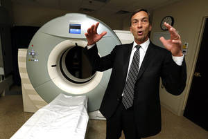 Photo - Local neurosurgeon Robert Remondino talks about a CT scanner at the Oklahoma Spine Hospital during a recent tour of the facility. Photo by Steve Sisney, The Oklahoman