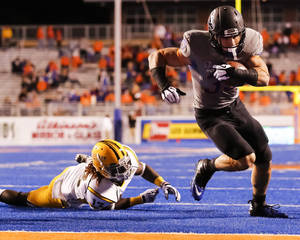 Photo - Boise State running back Charles Bertoli (35) runs the ball past Southern Mississippi defensive back Chris Cooley (13) during the second half of an NCAA college football game in Boise, Idaho, Saturday, Sept. 28, 2013. Boise State won 60-7. (AP Photo/Otto Kitsinger)
