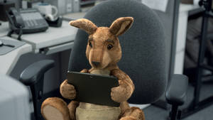 Photo -  A frame grab from Dish's commercial where a Kanagroo watches NCAA basketball action on a tablet. Dish Network Corp. started running new ads Tuesday  that tout how well its Hopper digital video recorder can help customers sneak in some game-watching at work, by streaming to a tablet. AP Photo  <strong> -  AP </strong>