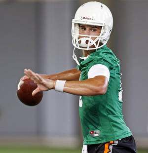 Photo - Oklahoma State quarterback Mason Rudolph (10) throws the ball during the first team practice of the fall at the Sherman E. Smith Training Facility on the campus of Oklahoma State University in Stillwater on August 1, 2014. Photo by KT King, The Oklahoman