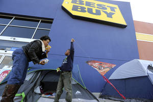 Photo -   FILE -In this Monday, Nov. 19, 2012, file photo, Denise Smith-Lad, left, asks her grandson Jordan Smith, 6, what he would like to eat as they camp in front of a Best Buy store in Cockrell Hill, Texas. Best Buy Co. reported another dismal quarter on Tuesday, Nov. 20, 2012, recording a loss in the third quarter, hurt by a continued sales slump and charges related to restructuring. Shares fell 5 percent in premarket trading. The electronics chain is struggling to reverse a years long decline in its business as competition from online stores and discounters increases, and consumers' tastes shift from more profitable items like TVs and desktop computers toward less profitable smartphones and tablets. (AP Photo/LM Otero)